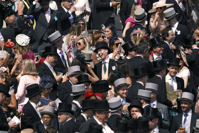 Looks more like a Fred Astaire movie than a racetrack: Racegoers traditionally dressed in the stands during Derby Day of the Derby Festival in Epsom England, Saturday June 1, 2019. The Derby is one of the premier events in the world horse race calendar. (John Walton/PA via AP)
