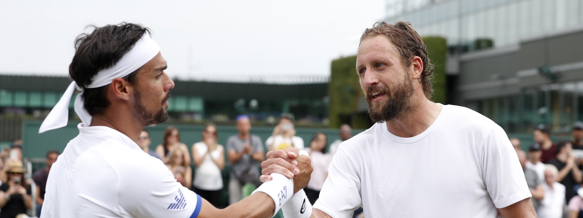 United States' Tennys Sandgren, right, greets Italy's Fabio Fognini at the net after winning their Men's singles match during day six of the Wimbledon Tennis Championships in London, Saturday, July 6, 2019. (AP Photo/Alastair Grant)