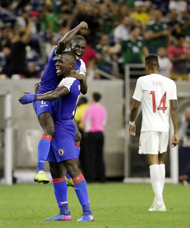 Haiti defender Carlens Arcus is held up by defender Andrew Jean Baptiste as Canada defender Mark-Anthony Kaye (14) walks off the field after Haiti defeated Canada 3-2 in a CONCACAF Gold Cup soccer quarterfinal Saturday, June 29, 2019, in Houston. (AP Photo/Michael Wyke)