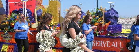 "This June 28, 2019 photo shows ""money girls"" walking alongside a float for the Hard Rock casino in Atlantic City N.J. a year after it opened. Extra money from sports betting helped New Jersey's casinos and racetracks win nearly $284 million in June, up 21.5 percent from a year ago."