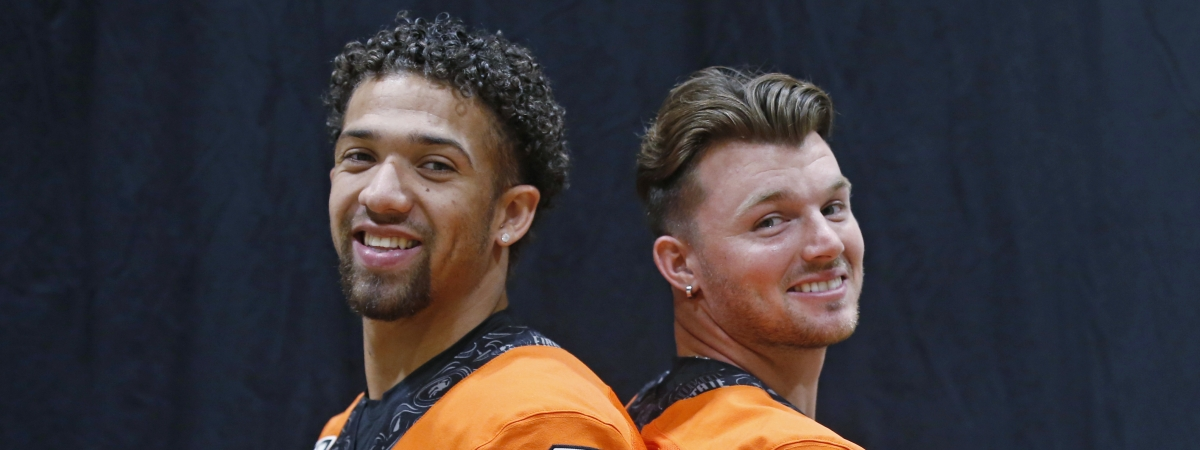 FILE - In this Saturday, Aug. 3, 2019, file photo, Oklahoma State quarterbacks Spencer Sanders, left, and Dru Brown pose for a photo during the NCAA college football team's media day in Stillwater Okla. Oklahoma State hasn't named a starting quarterback yet for its season opener next Friday night at Oregon State, as coach Mike Gundy continues to evaluate redshirt freshman Spencer Sanders and Hawaii grad transfer Dru Brown for the job. At this point, it seems likely that both will see action. (AP Photo/Sue Ogrocki, File)
