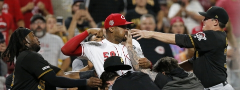 Cincinnati Reds relief pitcher Amir Garrett (50) throws punches as he is held back by a number of Pittsburgh Pirates players during a bench clearing brawl between the Reds and the Pirates at Great American Ball Park on Tuesday, July 30, 2019. (Sam Greene/The Cincinnati Enquirer via AP)
