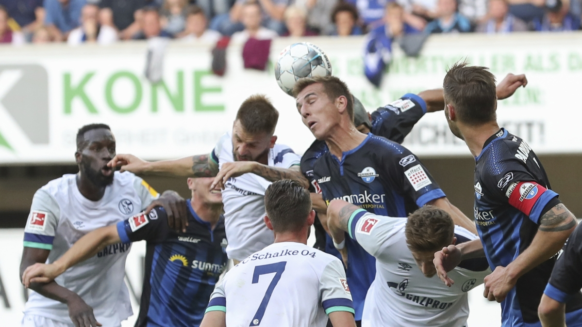 Paderborn's Uwe Hunemeier, center right, heads the ball in front of Schalke's Guido Burgstaller, center left, during the German Bundesliga soccer match between SC Paderborn 07 and FC Schalke 04 in the Benteler-Arena in Paderborn, Germany, Sunday Sept. 15, 2019.