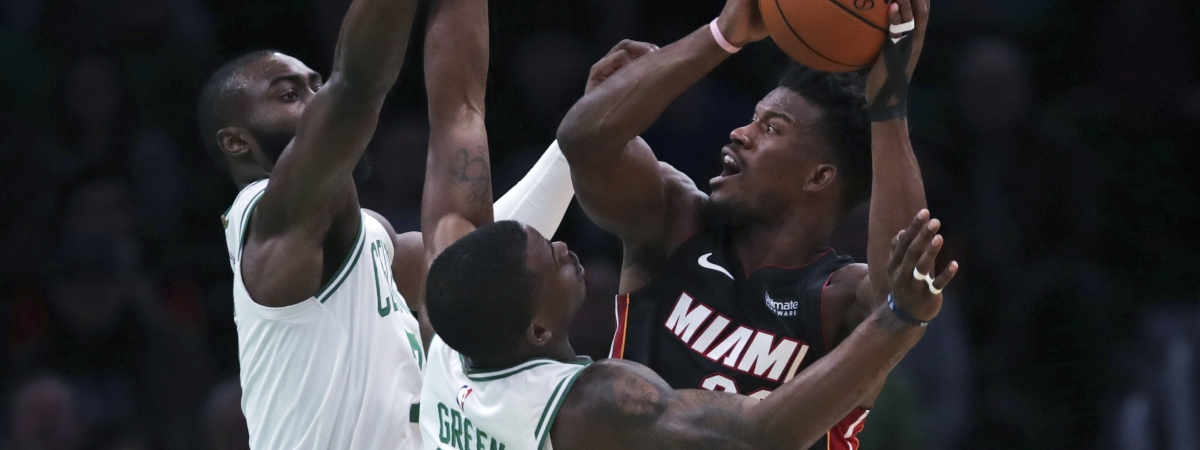 In this Dec. 4, 2019 file photo, Miami Heat forward Jimmy Butler, right, is covered on his shot by Boston Celtics guard Javonte Green (43) and forward Jaylen Brown, rear left, during the first half of an NBA basketball game in Boston.
