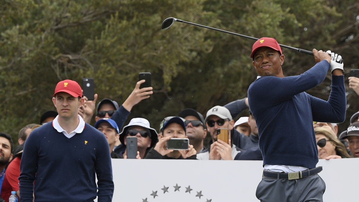 USA's Patrick Cantlay, left, watches as captain Tiger Woods tees off during a practice session ahead of the President's Cup Golf tournament in Melbourne, Tuesday, Dec. 10, 2019.