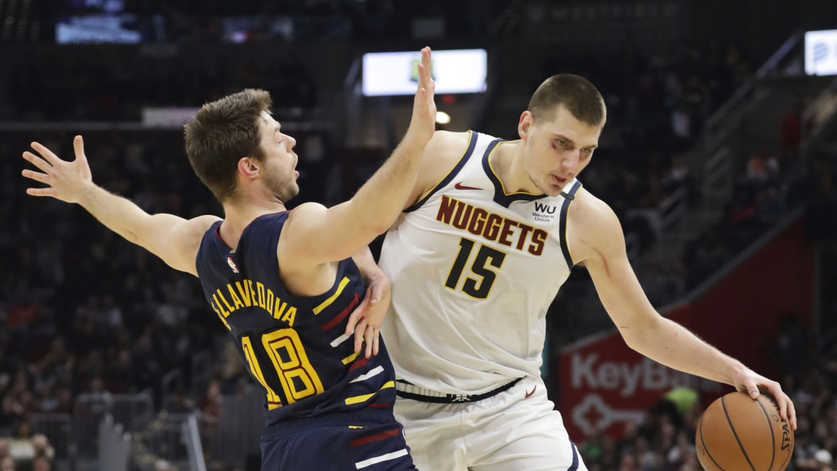 Denver Nuggets' Nikola Jokic (15) drives past Cleveland Cavaliers' Matthew Dellavedova (18) in the second half of an NBA basketball game, Saturday, March 7, 2020, in Cleveland. The Cavaliers won 104-102. (AP Photo/Tony Dejak)