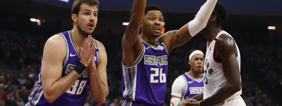 Sacramento Kings' Nemanja Bjelica, left, and Kent Bazemore, center, react after Bazemore was called for fouling Toronto Raptors forward Pascal Siakam, right, during the first quarter of an NBA basketball game in Sacramento, Calif., Sunday, March 8, 2020. (AP Photo/Rich Pedroncelli)