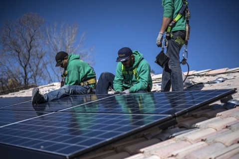 Workers installing SolarCity solar panels on a roof ( Photographer: Sergio Flores/ Bloomberg)