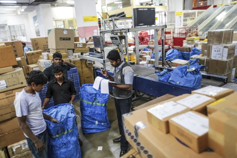Employees sort parcels during the overnight sort at a goods storage facility (Photographer: Dhiraj Singh/Bloomberg)