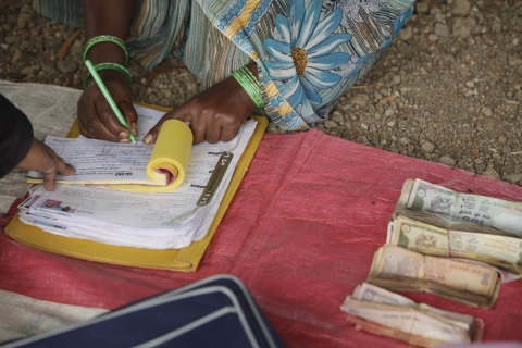 A woman signs a register to receive a loan during a meeting organized by SKS Microfinance Ltd. (Photographer: Adeel Halim/Bloomberg)