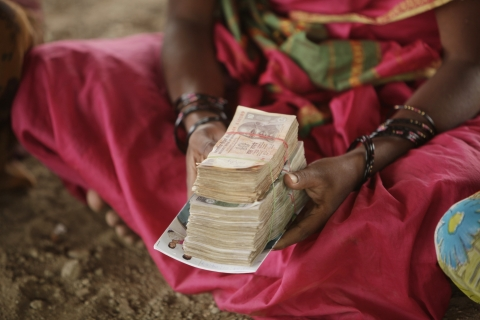 A woman holds the loan she has received. (Photographer: Adeel Halim/Bloomberg)
