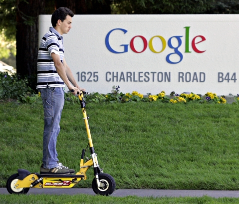 A man on an electric scooter passes by Google Inc.'s headquarters (Photographer: Kimberly White/Bloomberg News.)