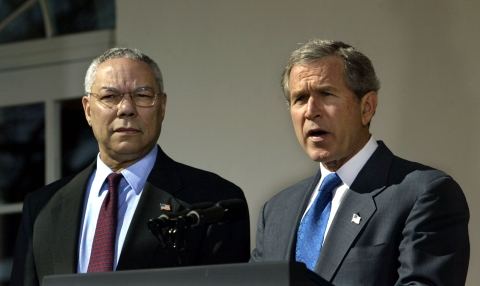 United States President George W Bush, right, speaks in the Rose Garden of the White House in Washington, DC on March 14, 2003 as Secretary of State Colin Powell looks on. (Photographer: Chris Kleponis/Bloomberg News)