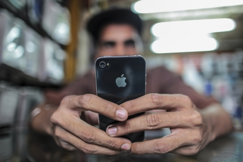 A man operates a Apple Inc. iPhone at a mobile phone store in this arranged photograph (Photographer: Dhiraj Singh/Bloomberg)