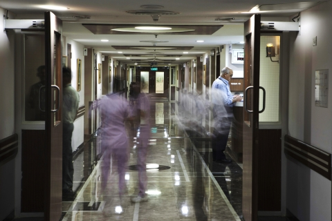 People move through the corridor of a patient ward at a hospital. (Photographer: Prashanth Vishwanathan/Bloomberg)