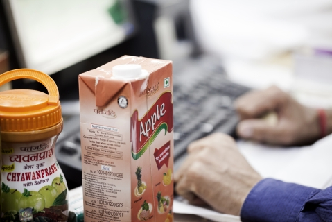 A container of chyawanprash and a carton of apple juice sit on a counter at a Patanjali Ayurved Ltd. store. (Photographer: Udit Kulshrestha/Bloomberg)