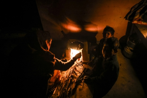 A woman cooks on a stove in the light provided by a kerosene lamp in her home at night in the village of Fateh Nagla, Uttar Pradesh, India, on January 14, 2017. (Photographer: Prashanth Vishwanathan/Bloomberg)