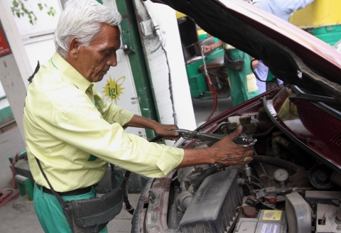 An Indraprastha Gas Ltd. attendant fills up a customer's car with compressed natural gas (CNG) at a station in New Delhi, India (Photographer: Pankaj Nangia/Bloomberg)