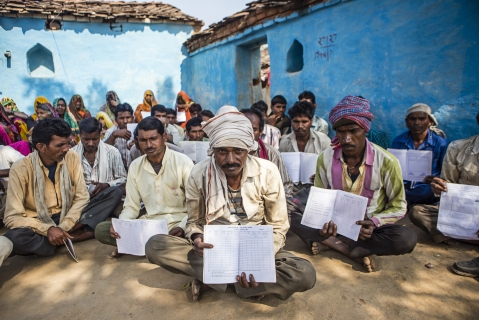 Villagers hold up their job cards with no entries for the rural jobs program, during a public hearing in the village of Lar Sauryana in Tikamgarh, Madhya Pradesh, India. (Photographer: Prashanth Vishwanathan/Bloomberg)