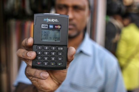 A vendor holds an Mswipe terminal, operated by M-Swipe Technologies Pvt Ltd., in an arranged photograph at a roadside stall in Bengaluru, India. (Photographer: Dhiraj Singh/Bloomberg)