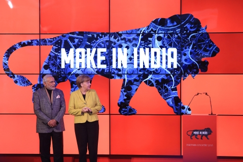 "Angela Merkel, Germany's chancellor, right, and Narendra Modi, India's prime minister, stand on stage as a ""Make In India"" logo is displayed at the Hanover industrial fair in Hanover, Germany. (Photographer: Krisztian Bocsi/Bloomberg)"