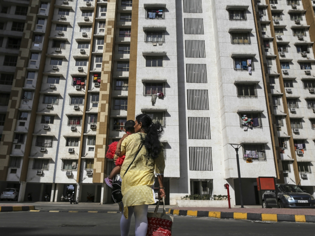 A pedestrian carries a child across a road in front of residential apartment buildings in Palava City on the outskirts of Mumbai. (Photographer: Dhiraj Singh/Bloomberg)