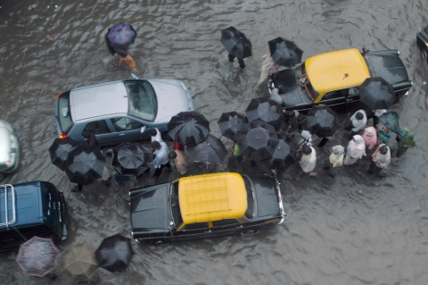 Pedestrians and traffic walk through a monsoon rains-flooded street in Mumbai, India. (Photographer: Santosh Verma/Bloomberg News)
