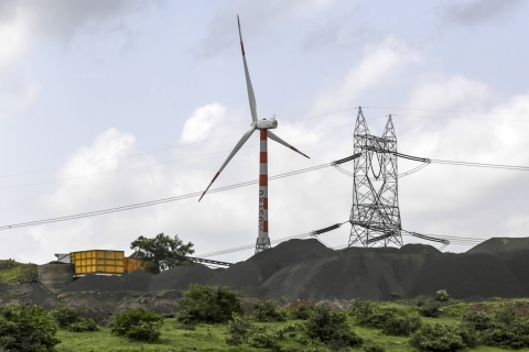 A wind turbine manufactured by Suzlon Energy Ltd. operates beyond an electricity pylon and coal pile at the Ostro Energy Pvt. Dewas Wind Project in Dewas, Madhya Pradesh. (Source: Dhiraj Singh/Bloomberg)