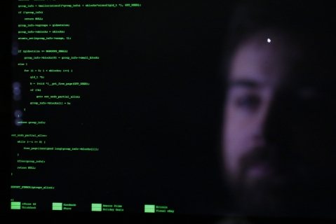 The face of an attendee is reflected in a laptop computer screen alongside code as he participates in the TechCrunch Disrupt London 2015 Hackathon in London, U.K. (Photographer: Luke MacGregor/Bloomberg)
