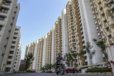 A motorcyclist ride past residential apartment buildings on the outskirts of Mumbai, India. (Photographer: Dhiraj Singh/Bloomberg)