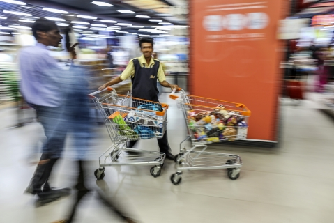 An employee pushes shopping carts (Photographer: Dhiraj Singh/Bloomberg)