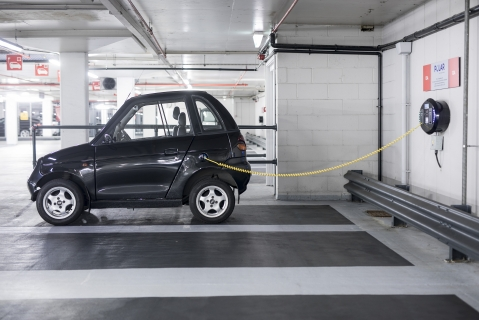 A charging plug connects an electric vehicle (EV) to a charging station at Q-Park Park Lane underground parking lot in London (Photographer: Simon Dawson/Bloomberg)