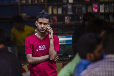 A man speaks on a mobile phone outside a mobile phone store in New Delhi. (Photographer: Prashanth Vishwanathan/Bloomberg)