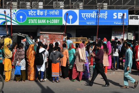 People wait in line outside a State Bank of India (SBI) branch in Delhi (Photographer: Anindito Mukherjee/Bloomberg)