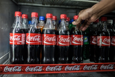 Coca-Cola beverages are placed on a shelf in a store in New Delhi, India. (Photographer: Sanjit Das/Bloomberg)