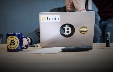 An employee uses a laptop computer branded with bitcoin logos. (Photographer: Christophe Morin/Bloomberg)