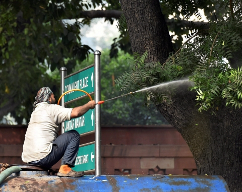 An NDMC worker sprays water on a tree to combat toxic smog and dust, and improve the air quality of the capital. (Image: PTI Photo)
