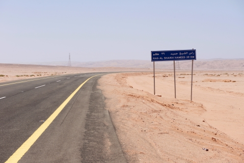 A road sign sits beside a desert highway indicating the distance to the bay at Ras Hameed, where the new mega-city of Neom is planned, Saudi Arabia, on February 26, 2016. (Photographer: Glen Carey/Bloomberg)