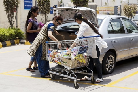 Customers load a car with goods from their shopping cart in the parking lot (Photographer: Udit Kulshrestha/Bloomberg)