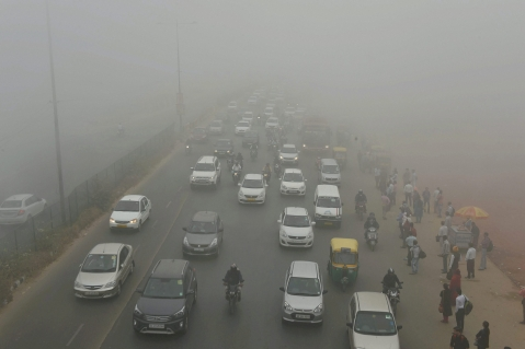 Vehicles plying at a road in smog, in New Delhi on Wednesday morning. (Image: PTI)