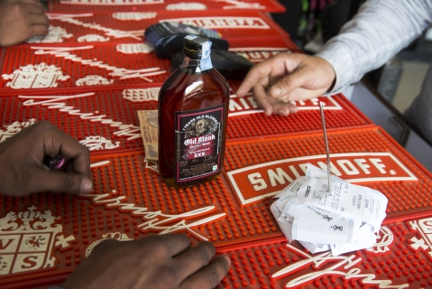 A customer purchases a bottle of Old Monk rum at a roadside liquor store in Gurgaon, Haryana. (Photographer: Udit Kulshrestha/Bloomberg)