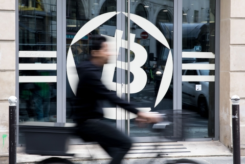 A cyclist passes the entrance to the La Maison du Bitcoin bank in Paris, France. (Photographer: Christophe Morin/Bloomberg)