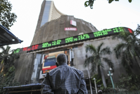 A man looks up at an electronic ticker board that indicates stock figures at the Bombay Stock Exchange (BSE) in Mumbai, India. (Photographer: Dhiraj Singh/Bloomberg)