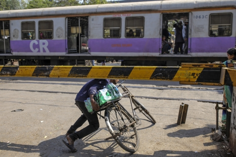 A cyclist ducks underneath the barrier of a railway crossing as a train travels past near Sewri railway station in Mumbai. (Photographer: Dhiraj Singh/Bloomberg)