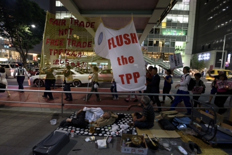 People carry banners during a protest against the Trans-Pacific Partnership trade agreement at the Shibuya district in Tokyo, Japan, on  May 26, 2015. (Photographer: Akio Kon/Bloomberg)