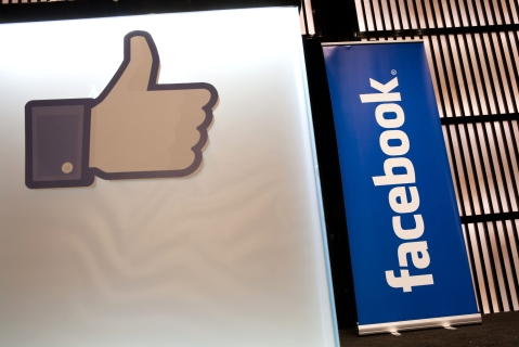 "A Facebook Inc. social media logo and a ""like"" symbol stand on display during a news conference. (Photographer: Duncan Chard/Bloomberg)"
