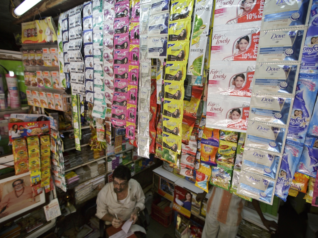 An attendant sits  at a kirana store in India. (Photographer: Kuni Takahashi/Bloomberg)