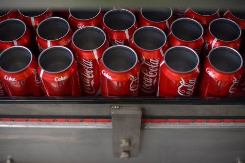 Empty Coca-Cola Classic cans move along a conveyor at a production facility. (Photographer: Carla Gottgens/Bloomberg)