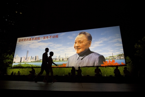 People walk past a portrait of China's former leader Deng Xiaoping in the Luohu district of Shenzhen, China. (Photographer: Brent Lewin/Bloomberg)