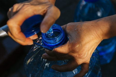 A resident fills a plastic bottle (Photographer: Waldo Swiegers/Bloomberg)